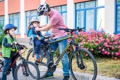 Familia que completa un ciclo, padre con la bici feliz del montar a caballo del niño al aire libre Foto de archivo libre de regalías