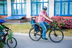 Familia que completa un ciclo, padre con la bici feliz del montar a caballo del niño al aire libre Foto de archivo