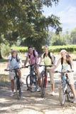 Familia que completa un ciclo a través de campo Foto de archivo libre de regalías