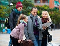 Familia que comprueba la dirección en mapa Fotos de archivo