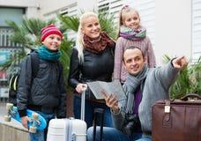 Familia que comprueba la dirección en mapa Imágenes de archivo libres de regalías