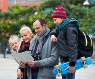 Familia que comprueba la dirección en mapa Foto de archivo