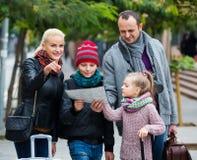 Familia que comprueba la dirección en mapa Fotografía de archivo
