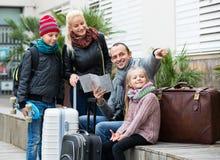 Familia que comprueba la dirección en mapa Imagenes de archivo