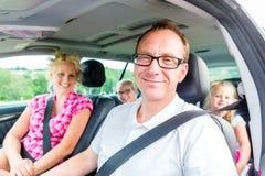Familia que conduce en coche con el cinturón de seguridad