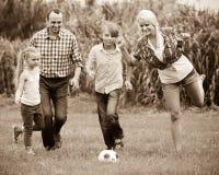 Familia que corre con la bola Imagen de archivo libre de regalías
