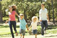 Familia que corre hacia cámara en parque del verano Fotos de archivo
