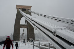 Familia que cruza puente colgante de Clifton en la nieve Fotografía de archivo