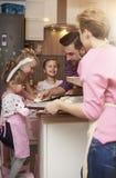 Familia que cuece en casa Imagen de archivo libre de regalías