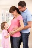 Familia que cuenta con al nuevo bebé Fotos de archivo