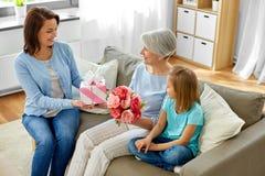 Familia que da el presente y las flores a la abuela fotos de archivo libres de regalías