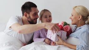 Familia que da las flores y el regalo a la madre en cama almacen de metraje de vídeo