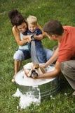 Familia que da a perro un baño. Fotografía de archivo