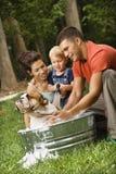 Familia que da a perro un baño. Imagen de archivo libre de regalías