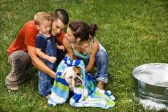 Familia que da a perro un baño. foto de archivo libre de regalías