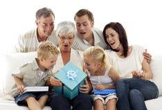 Familia que da un presente a la abuela Imágenes de archivo libres de regalías
