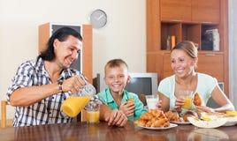 Familia que desayuna con el zumo de naranja en mañana Imagenes de archivo