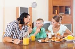 Familia que desayuna con los cruasanes y el jugo Foto de archivo