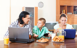 Familia que desayuna con los ordenadores portátiles y el jugo en mañana Fotos de archivo