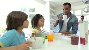 Familia que desayuna en cocina junto almacen de video