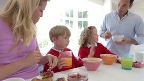 Familia que desayuna en cocina junto almacen de metraje de vídeo