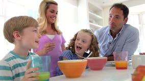 Familia que desayuna en cocina junto metrajes