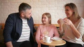Familia que descansa en café La familia es madre, padre e hija La gente se está sentando en la tabla Son feliz y sonrisa almacen de metraje de vídeo