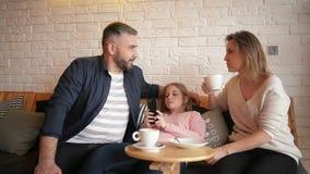 Familia que descansa en caf? La familia es madre, padre e hija La gente se est? sentando en la tabla Son feliz y sonrisa almacen de video