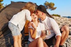Familia que descansa sobre costa rocosa, muchacha que alcanza hacia fuera la mano para dar a la madre del abrazo fotos de archivo