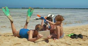 Familia que descansa sobre la playa almacen de metraje de vídeo