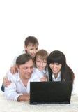 Familia que descansa un ordenador portátil Foto de archivo libre de regalías
