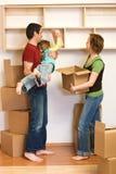 Familia que desempaqueta con las porciones de cajas de cartón Foto de archivo libre de regalías