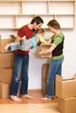 Familia que desempaqueta de porciones de cajas de cartón Fotos de archivo libres de regalías