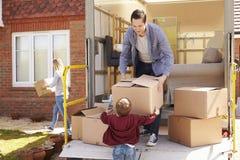 Familia que desempaqueta la mudanza en cajas desde el camión del retiro imagen de archivo libre de regalías