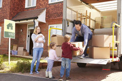 Familia que desempaqueta la mudanza en cajas desde el camión del retiro fotografía de archivo libre de regalías