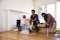 Familia que desempaqueta las cajas en nuevo hogar en día móvil foto de archivo