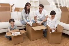 Familia que desempaqueta los rectángulos que mueven la casa Foto de archivo
