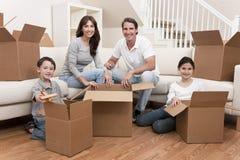 Familia que desempaqueta los rectángulos que mueven la casa Imágenes de archivo libres de regalías