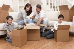 Familia que desempaqueta los rectángulos que mueven la casa Imagen de archivo libre de regalías
