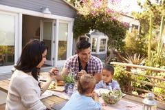 Familia que dice el jardín de Grace Before Outdoor Meal In Fotografía de archivo