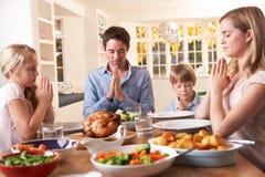 Familia que dice rezo antes de comer la cena de la carne asada Imagen de archivo libre de regalías