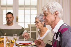 Familia que dice tolerancia antes de cena de la Navidad Imagenes de archivo