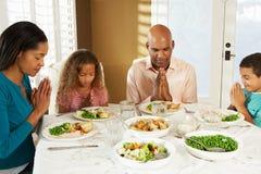 Familia que dice tolerancia antes de comida en casa Imágenes de archivo libres de regalías