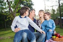 Familia que disfruta de comida campestre en parque Fotografía de archivo libre de regalías