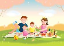 Familia que disfruta de comida campestre Se están sentando en la hierba en un parque, la cesta con la comida y los juguetes para  Foto de archivo libre de regalías