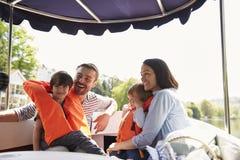Familia que disfruta de día hacia fuera en barco en el río junto imagen de archivo libre de regalías