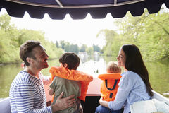 Familia que disfruta de día hacia fuera en barco en el río junto fotos de archivo libres de regalías