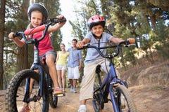 Familia que disfruta de la caminata en el campo con las bicis Fotos de archivo libres de regalías