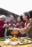Familia que disfruta de la comida china en ropa del chino tradicional Imágenes de archivo libres de regalías