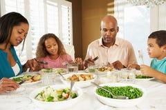 Familia que disfruta de la comida en casa Imágenes de archivo libres de regalías